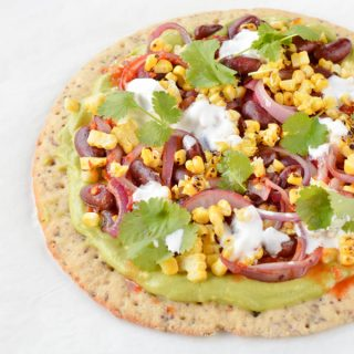 Skinny Avocado pizza with Mexican toppings and thin sprouted pizza base. An healthy pizza recipe ready in less than 15 minutes with delicious toppings: fried black beans, red onions, grilled corn, salsa sauce and coconut yogurt. Gluten free+ dairy free + skinny recipe.